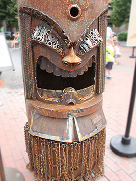 Large sculpture of a figure with an open mouth and chain skirt. 'Big Oily' was created by Tom Schell.